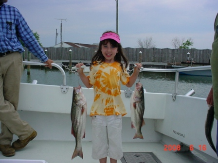 A young lady poses with her catch of the day. Two beautiful Maryland rockfish caught in June!